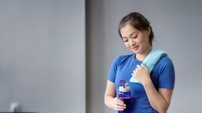 Portret sprawności fizycznej instruktora mienia uśmiechnięta Azjatycka żeńska butelka woda i ręcznikowa patrzeje kamera zbiory