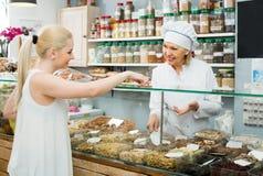 Portret sprzedawca i szczęśliwe dziewczyny kupienia dokrętki obraz stock