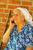 Portret stara kobieta opowiada na telefonie komórkowym outdoors nad 90 lat Fotografia Stock
