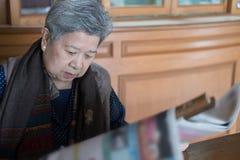 Portret stara kobieta, starsza kobieta, senior czyta gazetę Zdjęcia Royalty Free