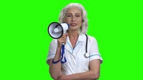 Portret starsza życzliwa lekarka opowiada w megafonie zbiory wideo