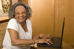 Portret starsza amerykanin afrykańskiego pochodzenia kobieta na jej komputerze zdjęcie stock