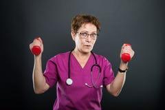 Portret starsza damy lekarka trzyma dwa dumbbells zdjęcia royalty free