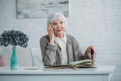 portret starsza kobieta opowiada na smartphone z chodzącym kijem podczas gdy siedzący przy stołem z albumem fotograficznym fotografia royalty free