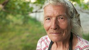 Portret starsza kobieta w chustce Wiatr waha się jej szarego włosy, patrzeje w kamerę i mruga zbiory wideo