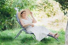 Portret starsza kobieta w kapeluszowym lying on the beach na sunbed Zdjęcia Stock