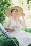 Portret starsza kobieta w kapeluszowym lying on the beach na sunbed Zdjęcia Royalty Free