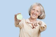 Portret starsza kobiety mienia wolontariusza odznaka przeciw błękitnemu tłu obraz royalty free
