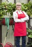 Portret starsza ogrodniczka z rękami krzyżował w szklarni Zdjęcie Royalty Free