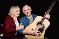 Portret starszego mężczyzna mienia gitara z żoną blisko obok Zdjęcie Stock