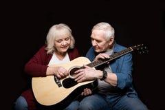 Portret starszego mężczyzna nauczania kobieta bawić się gitarę Obrazy Stock