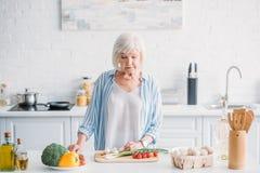 portret starszej damy tnący warzywa podczas gdy kulinarny gość restauracji przy kontuarem fotografia stock