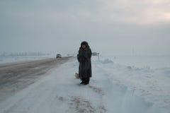 Portret starszej kobiety futerkowego żakieta i kapeluszu pozycja przy zima śniegiem zakrywał śródpolną drogę, telephoto Obrazy Stock