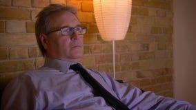 Portret starszy biznesmen w kostiumu chłodzi za TV przed po ciężkiego dnia roboczego jest baczny i rozbawiony zdjęcie wideo