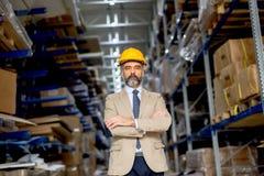 Portret starszy biznesmen w kostiumu z hełmem w warehous Fotografia Royalty Free