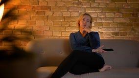 Portret starszy caucasian damy obsiadanie na kanapy i dopatrywania TV zamyśleniu w wygodnej domowej atmosferze obrazy stock