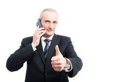 Portret starszy elegancki mężczyzna opowiada przy telefonem pokazuje jak zdjęcie stock