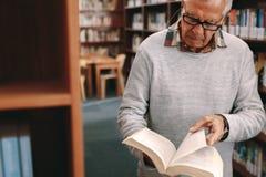 Portret starszy mężczyzna patrzeje książkę w bibliotece obraz royalty free