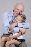 Portret starszy mężczyzna obejmuje wnuczki Zdjęcia Royalty Free