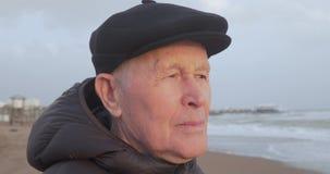 Portret starszy mężczyzna w płaskiej nakrętce i brąz pokrywamy pozycję na plaży zbiory wideo