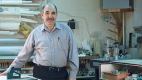 Portret starszy męski właściciel biznesu za kontuarem jego warsztat, pozycja i ono uśmiecha się kamera, Zdjęcia Royalty Free