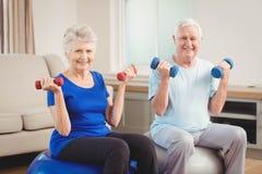 Portret starszy pary obsiadanie na sprawności fizycznych piłkach z dumbbells Zdjęcie Stock