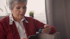 Portret starzejący się żeński konsumpcyjny pisać na maszynie numer karty kredytowej na smartphone ekranie zdjęcie wideo