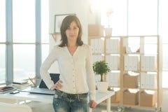 Portret stoi blisko miejsca pracy kobieta, patrzeje kamerę obrazy stock