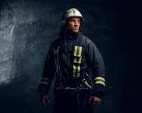 Portret strażak patrzeje z ukosa z ufnym spojrzeniem ubierał w jednolitym i zbawczym hełmie fotografia stock