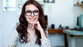 Portret strzelał atrakcyjna kobieta patrzeje kamerę i ono uśmiecha się podczas gdy pracujący w miastowym biurze z bliska zdjęcie wideo