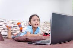 Portret strzelał azjatykcia mała dziewczynka używa laptop w domu Fotografia Royalty Free
