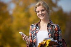 Portret studenckie strony zewnętrzne, trzyma telefon komórkowego w jeden ręce Obraz Royalty Free