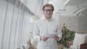 Portret succesvolle blonde mens in glazen die in een licht comfortabel document staan die van de bureauholding de camera bekijken stock videobeelden