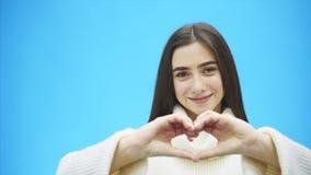 Portret szczęśliwa młoda kobieta jest ubranym białego ciepłego pulower Podczas ten czasu, ręka gest serce pokazuje i czuje zbiory