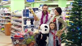 Portret szczęśliwa rodzina w supermarkecie przed bożymi narodzeniami zbiory wideo
