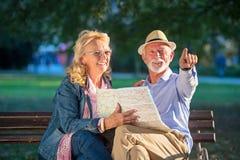 Portret szczęśliwy mężczyzny i kobiety czytanie kartografuje podczas gdy siedzący na parkowej ławce Starsza para na urlopowej uży obrazy stock