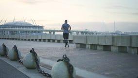 Portret szczęśliwy młody amerykanin afrykańskiego pochodzenia mężczyzny szkolenie jogging rasy słucha muzyka w Londyńskiej ulicie zbiory wideo