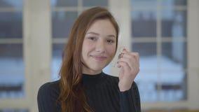 Portret szczęśliwa śliczna uśmiechnięta kobieta pokazuje klucze nabywający mieszkanie lub nowy dom kamera target31_1_ zdjęcie wideo