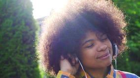 Portret szczęśliwa amerykanin afrykańskiego pochodzenia kobieta z Afro fryzurą w koszula i hełmofonach zdjęcie wideo