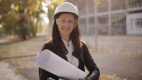 Portret Szczęśliwa fachowa budowa inżyniera kobieta trzyma projekt i jest ubranym zbawczego hełm i zbiory