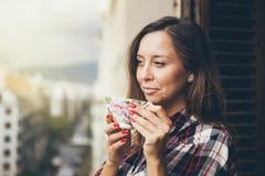 Portret szczęśliwa i uśmiechnięta kobieta pije kawę na balkonie z miasto widokiem Zdjęcia Stock