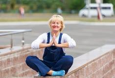 Portret szczęśliwa kobieta w jednolitym obsiadaniu w lotosowej pozie zdjęcia royalty free