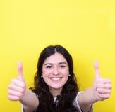 Portret szczęśliwa kobieta z aprobatami przeciw żółtemu tłu fotografia royalty free