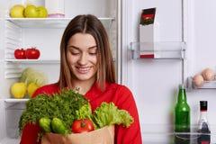 Portret szczęśliwa kobieta z rozochoconym wyrażeniem trzyma papierową torbę z pomidorami, cucmbers, koperem i sałatą, komes od sk zdjęcie royalty free