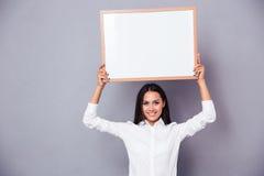 Portret szczęśliwa kobiety mienia pustego miejsca deska na głowie Fotografia Stock