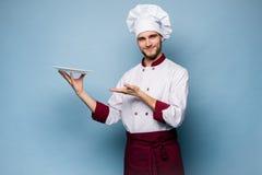 Portret szczęśliwa męska szefa kuchni kucharza pozycja z talerzem odizolowywającym na bławym tle zdjęcia royalty free
