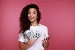 Portret szczęśliwa młoda afro amerykańska kobieta trzyma wiązkę pieniędzy banknoty i patrzeje telefon komórkowego odizolowywające zdjęcie royalty free