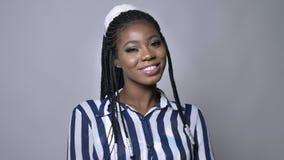 Portret szczęśliwa młoda afrykańska kobieta która jest uśmiechnięta w ruchu na szarym tle zbiory