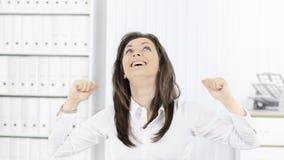 Portret szczęśliwa młoda biznesowa kobieta w biurze, ręki w górę obrazy stock