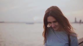 Portret szczęśliwa młoda Europejska dziewczyna pozuje, patrzeje kamerę z włosianym dmuchaniem w wiatrze przy zmierzch rzeki plażą zbiory